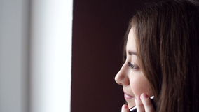 Woman looking out the window and talking on the phone stock video