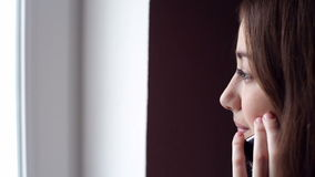 Woman looking out the window and talking on the phone stock video footage