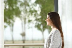 Woman looking outside through window at home. Happy woman looking outside through the window at home royalty free stock image