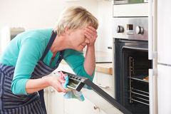 Woman Looking In Oven And Covering Eyes Over Disastrous Meal. Woman Looking In Oven And Covering Eyes Royalty Free Stock Photos