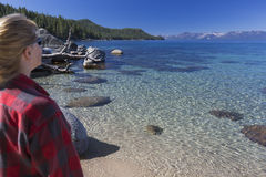 Woman Looking Over Beautiful Shoreline of Lake Tah. Woman Looking Over Beautiful Clear Water Shoreline of Lake Tahoe Royalty Free Stock Photography