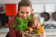 Woman looking over a burlap sac of fresh fall vegetables Royalty Free Stock Image