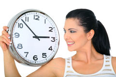 Woman Looking Over Clock. Happy smiling woman or mom looking at clock showing 3 o'clock royalty free stock photography