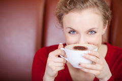 Woman looking over cup of cappuccino Stock Photo
