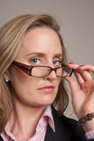 Woman looking over glasses. While holding them Royalty Free Stock Photography