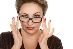 Woman looking over glasses. Portrait of a young woman looking over glasses against white background Stock Photo