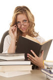 Woman looking over glasses book sitting Stock Image