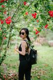 Woman Looking over Her Shoulder Wearing Black Sleeveless Top and Black Jeans Under a Red Hibiscus Plant at Daytime royalty free stock photos