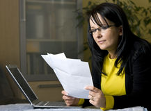 Woman looking over paperwork. A woman sitting at her computer and looking over paperwork or bills Royalty Free Stock Images