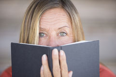 Woman looking over reading book cover Stock Images