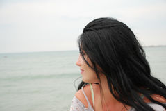 Woman looking over shoulder to ocean Royalty Free Stock Images