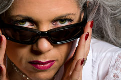 Woman looking over sunglasses Stock Photo