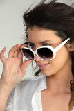 Woman looking over sunglasses Royalty Free Stock Images