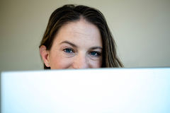 Woman looking over the top of her laptop screen Royalty Free Stock Photo