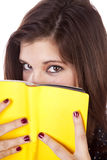 Woman looking over yellow book Royalty Free Stock Photos