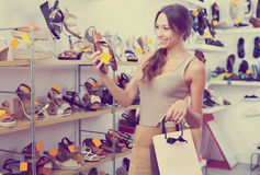 Woman looking after pair of shoes Royalty Free Stock Images