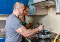 Woman looking into a pan her husband is holding in a kitchen Royalty Free Stock Photos