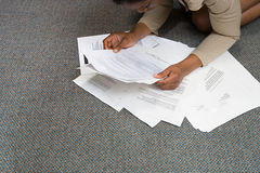 Woman looking at paperwork on floor Stock Photography