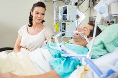 Woman Looking At Patient Resting On Bed Stock Photos