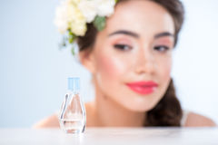 Woman looking at perfume. Woman looking at small perfume bottle, focus on foreground Stock Photography