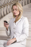 Woman looking at phone on stairs Royalty Free Stock Images