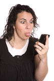 Woman looking a phone with tongue out Stock Photography