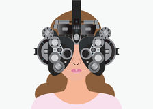 Woman looking through phoropter during eye exam. Royalty Free Stock Photo