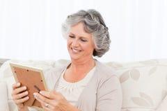 Woman looking at a photo Stock Photos