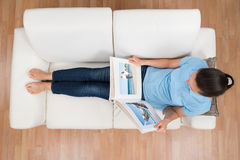 Woman Looking At Photo Album. High Angle View Of Young Woman Looking At Photo Album On Sofa Stock Image
