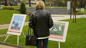 Woman looking at photography exhibit in park, openair gallery, country landscape. Stock footage stock video footage