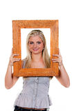 Woman looking through a picture frame Stock Photography