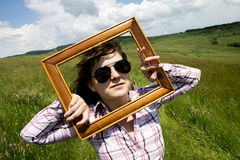 Woman looking through picture frame Stock Photography