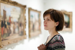 Woman looking pictures in museum royalty free stock photos