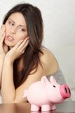 Woman looking at piggy bank. Finance - Young woman looking at piggy bank Stock Images