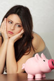 Woman looking at piggy bank Royalty Free Stock Photos