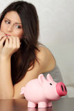 Woman looking at piggy bank Stock Photography