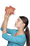 Woman looking at piggy bank to see if she has any money left Stock Images