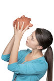 Woman looking at piggy bank to see if she has any money left Stock Image