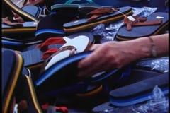 Woman looking through pile of flip flops stock video footage