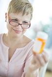 Woman Looking At Pill Bottle Stock Photography