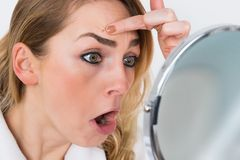Woman looking at pimple in mirror Stock Images