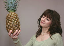 A woman looking a pineapple Royalty Free Stock Photos