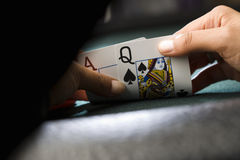 Woman looking at playing cards at poker table, close-up of hands Stock Images