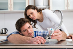 Woman Looking At Plumber Fixing Steel Tap Stock Images