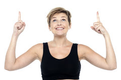 Woman looking and pointing upwards with both hands Royalty Free Stock Images