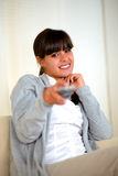 Woman looking and pointing at you with remote Stock Photo
