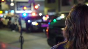 Woman looking at police in a night city