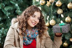 Woman Looking At Present Against Christmas Tree Royalty Free Stock Images