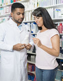 Woman Looking At Product Held By Chemist In Pharmacy Stock Images