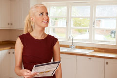Woman Looking At Property Details For New Home Stock Photo